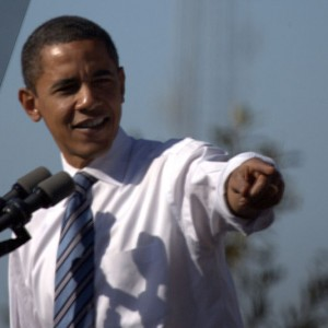 Barack Obama speaking into a microphone and pointing to the right - Photo by Pat Hawks
